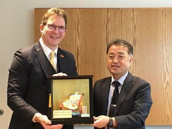 本学からの記念品を手にするトロッターランガラ学長と鈴木副学長